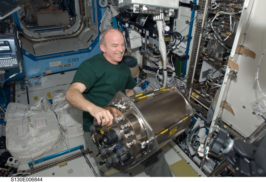 Astronaut Jeff Williams installs a Distillation Assembly into the Urine Processor Assembly on the ISS.