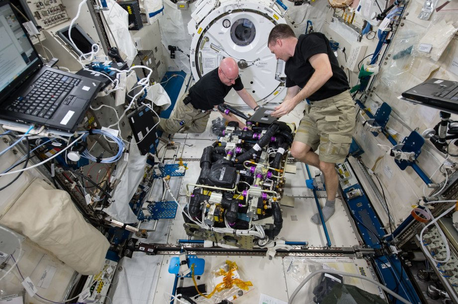 Astronauts Scott Kelly and Terry Virts are seen replacing a faulty fan on one of the space station's two Carbon Dioxide Removal Assemblies.