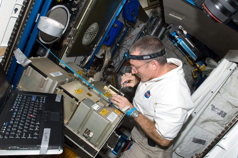 Astronaut Dan Burbank works on the mass spectrometer portion of the Major Constituent Analyzer, a tool that identifies the gasses that are present in the ISS's atmosphere.