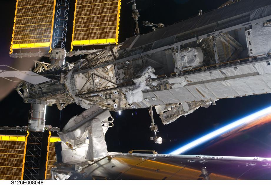 Astronaut Steve Bowen works to clean and lube one of the ISS's Solar Alpha Rotary Joints during the STS-126 mission.