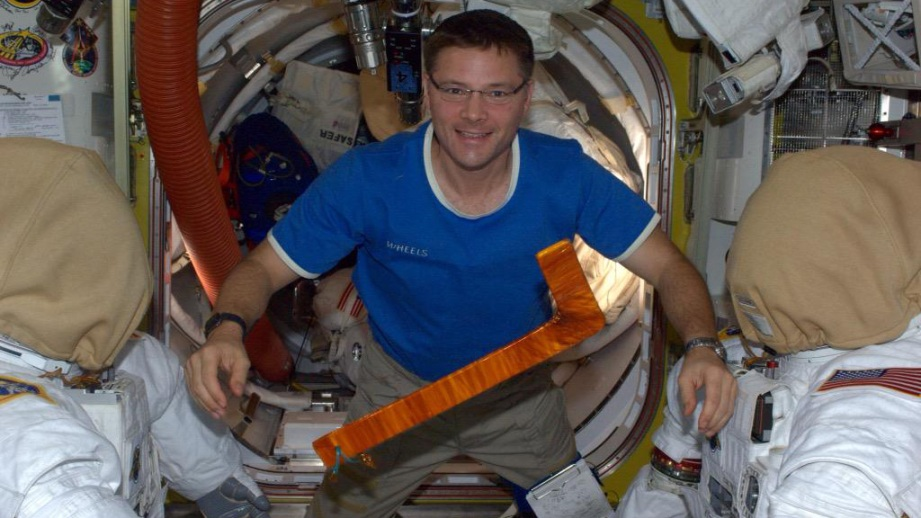 """Doug Wheelock shows off the improvised """"hockey stick"""" tool that was used by his spacewalking partner, Scott Parazynski, to untangle a snagged solar array."""