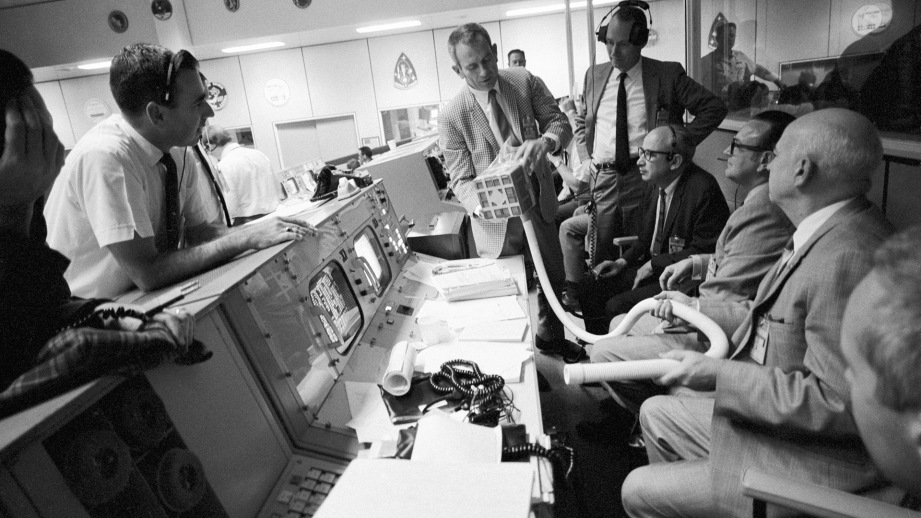 A crowd in mission control inspects the mailbox during the Apollo13 drama. The contraption was created on-the-fly to remove carbon dioxide from the lunar module.