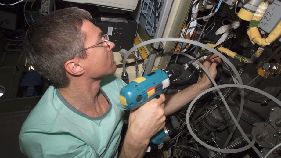 Cosmonaut Sergei Krikalev, Expedition 11 commander, uses a power tool as he makes repairs to the Elektron oxygen generator in the Zvezda Service Module of the International Space Station.
